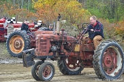 Dad on tractor, son waiting for his turn to compete.